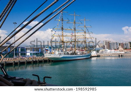 blue sky ,Sea port of Sochi . Clear summer day , blue sky and huge , white clouds near the pier there is a beautiful white three-masted sailing ship and small yachts - stock photo