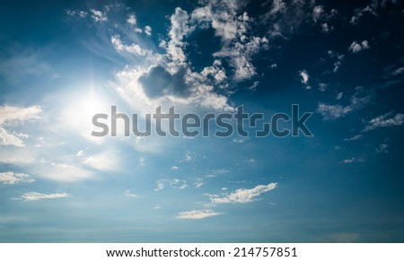 Blue sky with sun and clouds. With lens flare effect. - stock photo