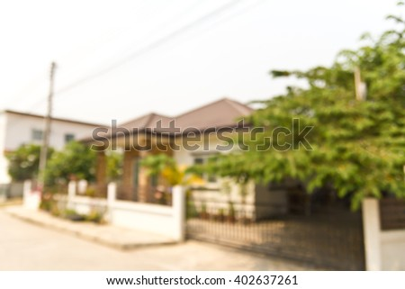 Blur image of large house of village with a big tree background - stock photo