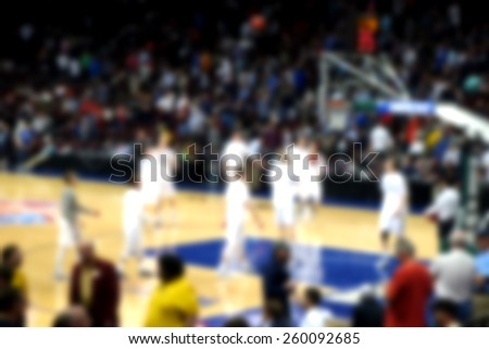blurred background of basketball crowd watching players practice before game                     - stock photo