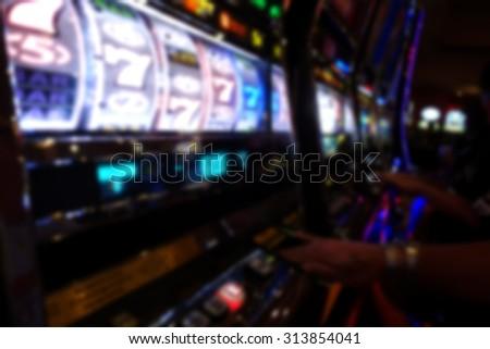 blurred background of hands playing casino slot machines                               - stock photo