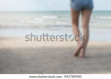 Blurred her vision Girl wearing Denim Shorts' Legs Walking on Beach