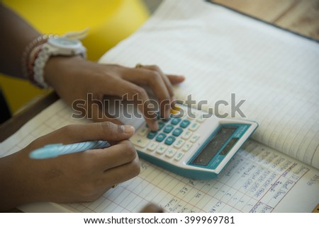 Blurred of hands holding pencil and pressing calculator buttons over documents - stock photo