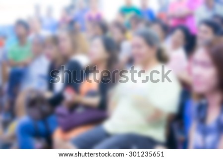 blurred people at show in hall for background usage