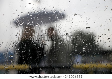Blurry snowy and rainy people with umbrella - stock photo