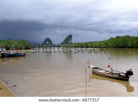 boats in krabi thailand before storm - stock photo