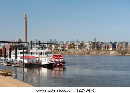 Boats on the Mississippi River with residential houses in the background - stock photo