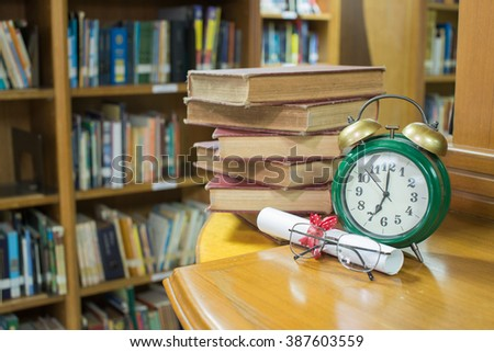 Book and graduation scroll  with Clock and glass,Education concept - stock photo