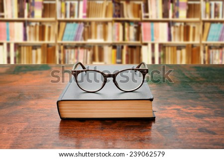 book with glasses on the desk against library  - stock photo