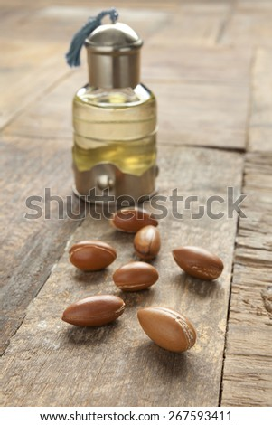 Bottle of argan oil and nuts on the table - stock photo