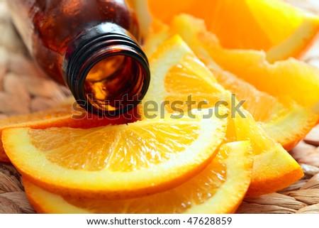 bottle of aromatic essence and fresh oranges - stock photo
