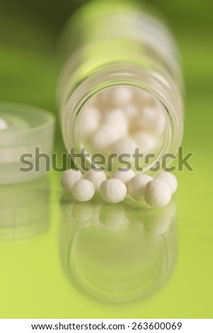 bottle with homeopathy globules in  green background  - stock photo