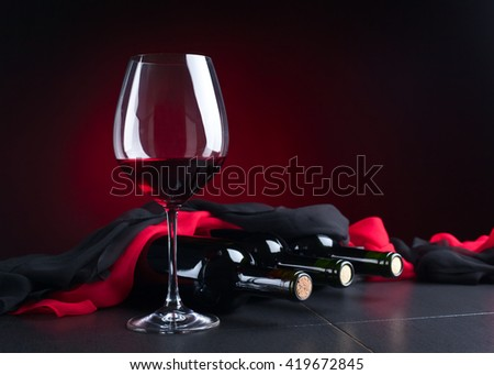 bottles and glass of red wine on  black table - stock photo