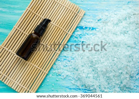 bottles essential oil and sea salt on a blue wooden table, Spa with - stock photo