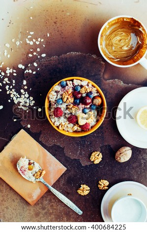 Bowl of oatmeal porridge with blueberry, close up. Healthy home made oatmeal porridge muesli with kefir yogurt and topped with blackberries, cherries and nuts. Served on a rustic wooden table.  - stock photo