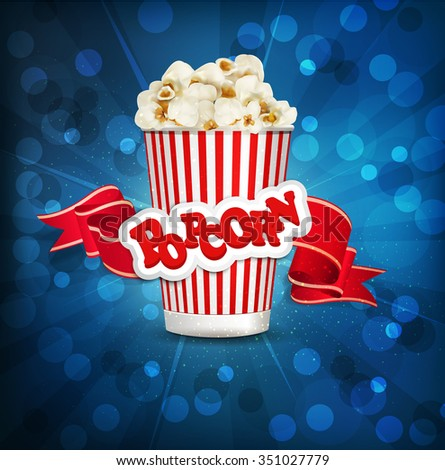 box with popcorn on a blue background with a bright red ribbon. - stock photo
