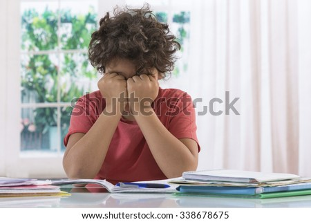 Boy exasperated with his homework - stock photo