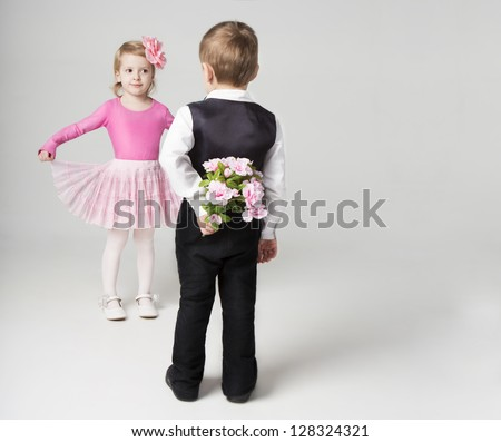 Boy hiding behind a flowers. Going to give a girl a bouquet. Girl is flirting. Studio shot. Gray background. Sweet relationship. - stock photo