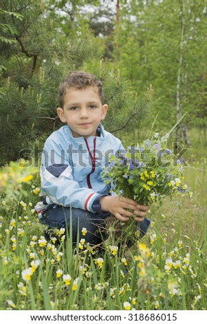Boy in a pine forest holding a bouquet of flowers.