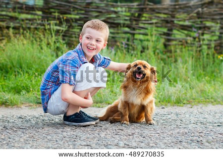 boy in a plaid shirt hugging a red fluffy dog. Best friends. Outdoor