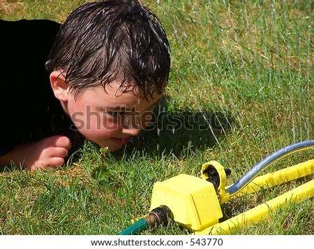 boy in a sprinkler - stock photo