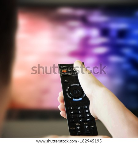boy is watching a television screen with his back - stock photo