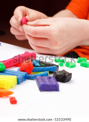 Boy moulds from plasticine on table - stock photo