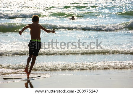 Boy moves on the surf board (alongside the sea shore) and a man swimming in the waves. Back view. (Brittany, France)  Freedom concept. - stock photo