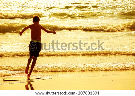 Boy moves on the surf board (alongside the sea shore) at sunset. Back view. (Brittany, France) Toned photo. Freedom concept. - stock photo