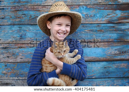 boy playing with a auburn cat outdoors - stock photo