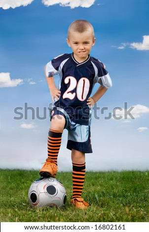 boy posing with football ball in the field - stock photo