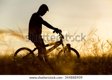 boy sat down on a bicycle in the area of strong sunlight.