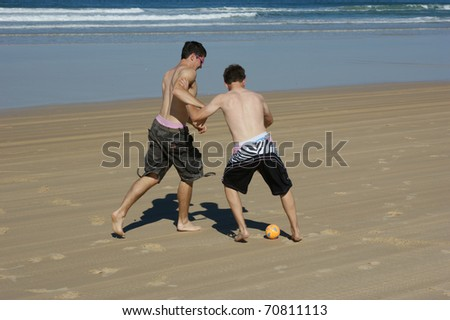 2 boys playing soccer on the beach - stock photo
