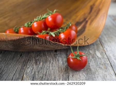 branch of fresh ripe cherry tomatoes on wooden background with selective focus - stock photo