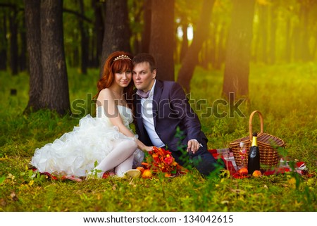 bride and groom newlyweds at a wedding outdoors in a green forest sitting on a picnic on the grass on a plaid blanket