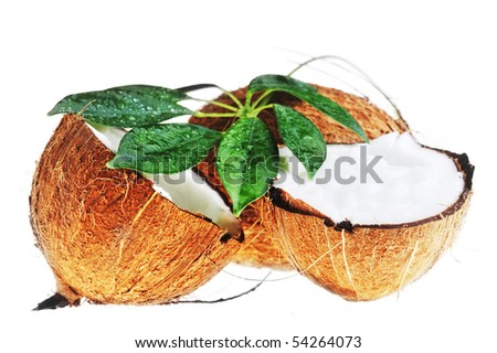 broken ripe coconut and leaves on white close up - stock photo