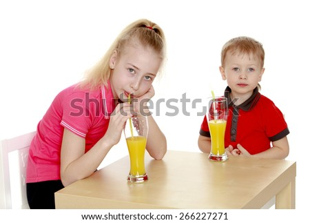 Brother sister drink juice sitting at the table.- isolated on white background