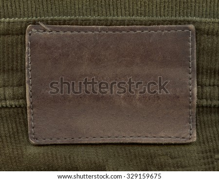 brown  leather label on green textile background