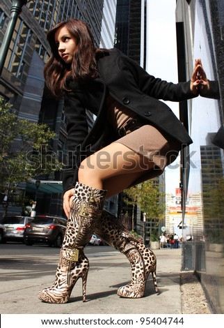 brunette girl in sexy boots posing in the city
