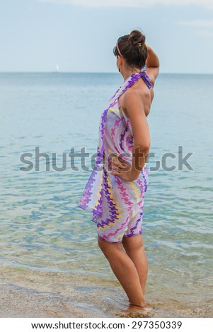 brunette woman in summer dress standing on beach and looking to the sea - stock photo