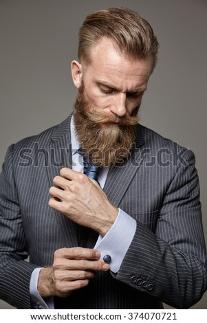 brutal man with beard in classic suit in modern style portrait - stock photo