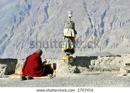 Buddhist monk reading a religious text with Himalaya mountains background - stock photo