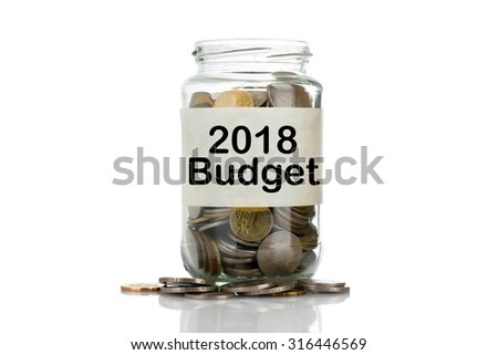 """2018 Budget"" text label on full coins of jar spill out from it isolated on white background - saving, donation, financial, future investment and insurance concept - stock photo"