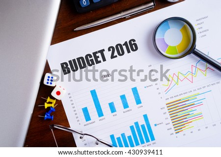 """""""Budget 2016"""" text on paper sheet with magnifying glass on chart, dice, spectacles, pen, laptop and blue and yellow push pin on wooden table - business, banking, finance and investment concept - stock photo"""
