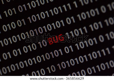 'Bug' word in the middle of the computer screen surrounded by numbers zero and one. Image is taken in a small angle.