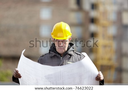 builder with blueprints on construction site - stock photo