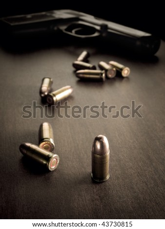 bullets with handgun in the back of the scene with focus on the bullet,sepia toned, closeup with vignette, useful for various security,protection or criminal topics - stock photo