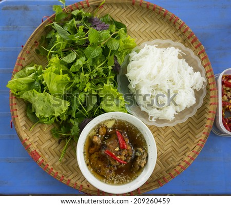 """Bun cha"" - the famous vietnamese noodle soup with bbq meat, spring roll, vermicelli and fresh vegetable served on bamboo flat basket - stock photo"