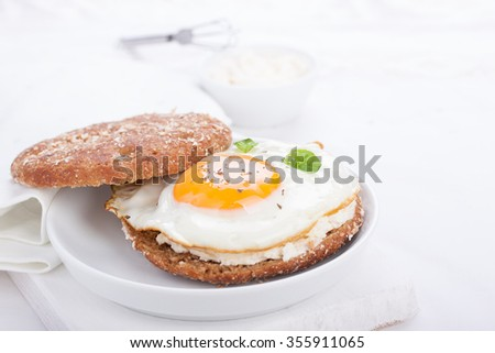Bun with egg, cottage cheese and fresh basil on a white plate for breakfast. selective focus, horizontal