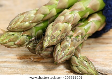 bunch of fresh uncooked asparagus spears on a wooden board                            - stock photo